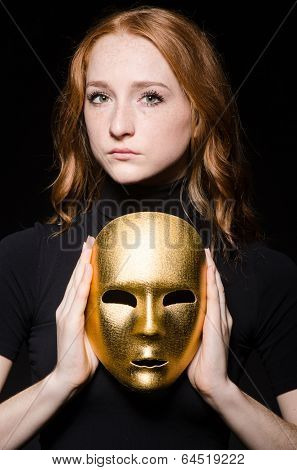 Redhead woman iwith mask in hypocrisy consept against black  background