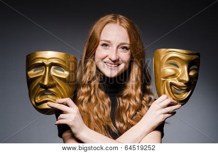 Redhead woman iwith masks in hypocrisy consept against grey background