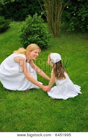 Young mother and daughter playing in meadow