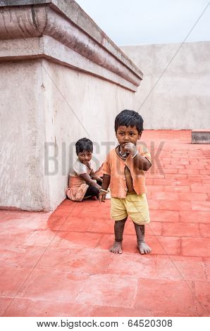 THANJAVUR, INDIA - FEBRUARY 14: Unidentified children, a boy and a girl on the roof of the temple February 14, 2013 in Thanjavur, India. Poverty in India is widespread, a third of the world's poor.
