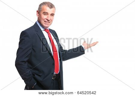 mid aged business man presenting something in the back while holding a hand in his pocket and smiling for the camera. isolated on a white background