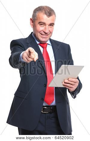 mid aged business man holding a tablet in his hand while pointing and looking at the camera with a smile on his face. isolated on a white background