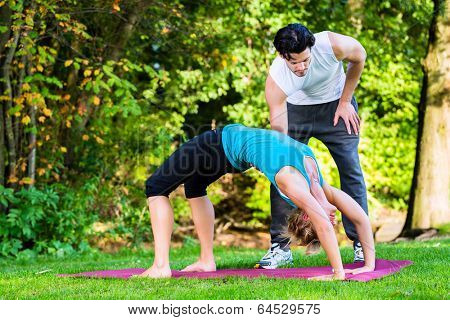 Young woman in city park doing yoga or warming up for exercising with her personal trainer or teacher