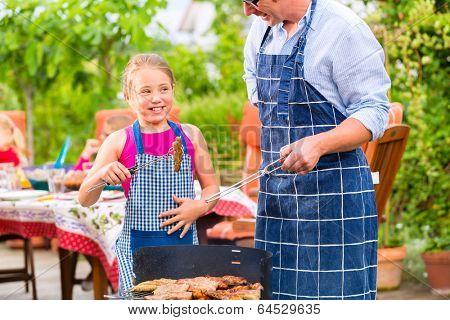 Father and daughter making barbecue in the garden in summer with sausages and meat