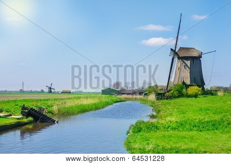 Traditional Dutch countryside - ditch, farm and windmill