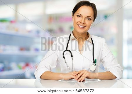 Young positive brunette doctor woman behind table in drug store