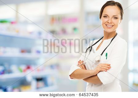 Young positive brunette doctor woman in drug store