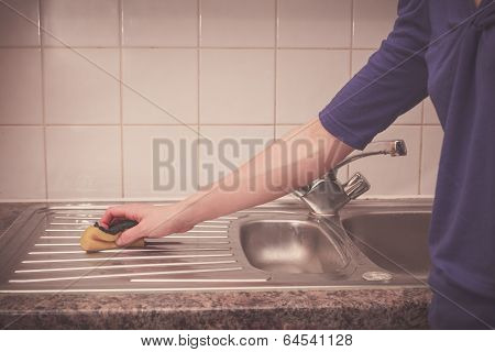 Woman Cleaning Around The Kitchen Sink