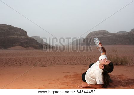 Desperate man in the desert drinking last drops of water from an empty bottle