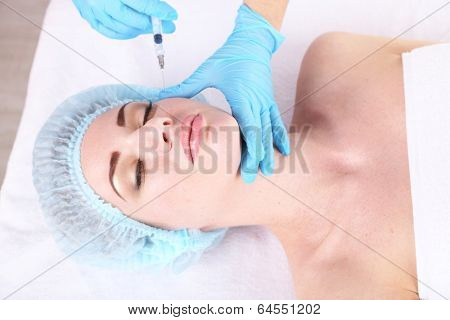 Woman in beauty clinic getting botox injection, on light background