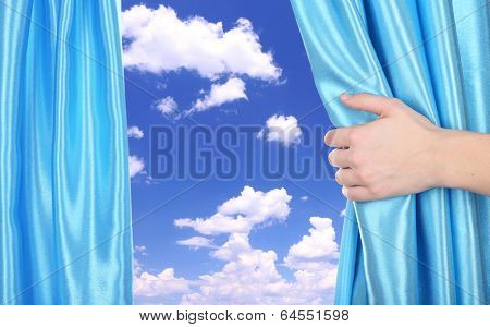 Hand opening curtain on sky background