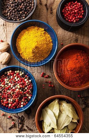 spices in bowls: pink black pepper, paprika powder, curry, bay leaf