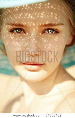 Beauty portrait of a beautiful woman in hat close-up. Beauty portrait of a trendy girl with rays of the sun on her face