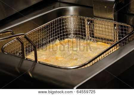 french fries being cooked in electric fryer