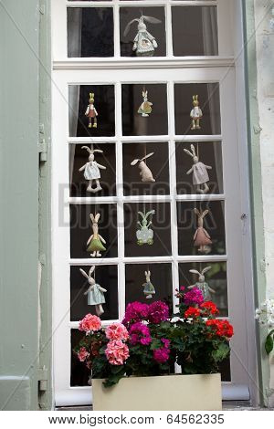 White window with flower pot and with funny hanging dollies