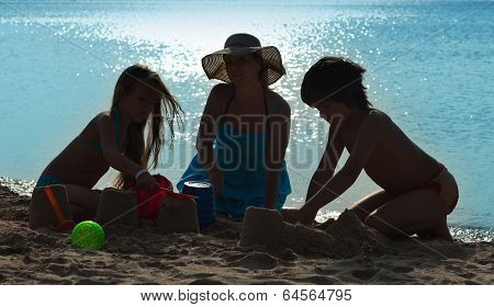 Family Playing On The Beach - Silhouettes