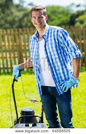 portrait of young man standing with lawnmower at home garden