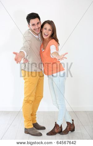 Cheerful couple spreading arms towards camera