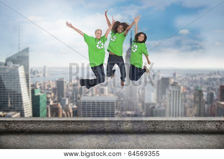 Enviromental activists jumping and smiling against balcony overlooking city