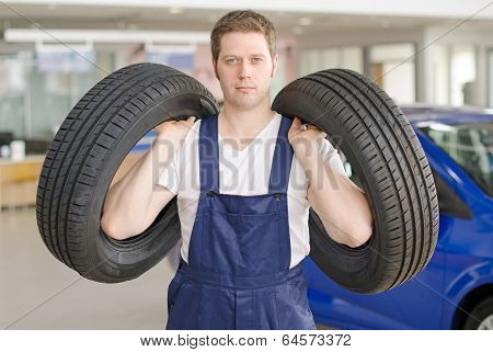 Young Mechanic With Tires In Service Center.