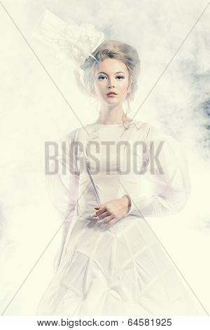 Portrait of a beautiful fashion model in the refined white dress and elegant hat. Snow queen. Winter fantasy.