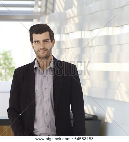 Portrait of confident businessman at office, looking at camera. Copyspace.