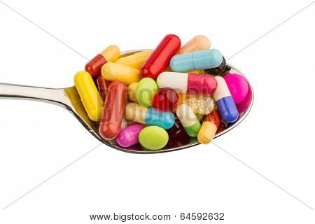 many colorful pills on a spoon. symbolic photo for tablets addiction and abuse of drugs.