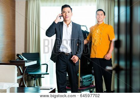 Portrait of guest and bell boy in hotel room