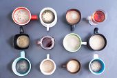 image of brew  - Time for a coffee break or teatime for office with a neat line up of dfifferent mugs handles looking diffrent directions freshly brewed foamy coffee and teas for a daily dose of caffeine to energize your day view from above - JPG