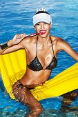 foto of mattress  - Woman with tanned body sitting on yellow air mattress in the pool in summer and licking lollipop  - JPG