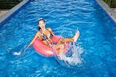 stock photo of flesh air  - naughty girl floating in an pink inner tube in a swimming pool and laughing - JPG