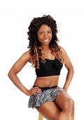 stock photo of mini-skirt  - A close picture of a young Jamaican woman in a silver mini skirt with