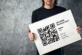 pic of qr codes  - Man holding QR code business card with personal data - JPG