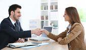stock photo of handshake  - Woman giving handshake to financial adviser - JPG