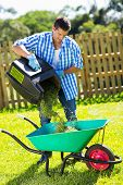 foto of grass-cutter  - young man emptying lawnmower grass into a wheelbarrow after mowing - JPG
