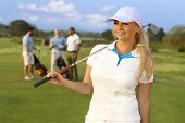 image of natural blonde  - Portrait of pretty blonde female golfer with golf club - JPG