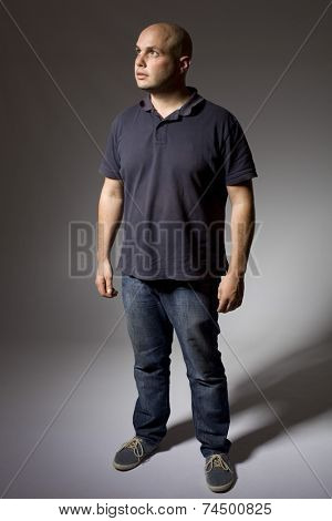 young man thinking full length on a dark background
