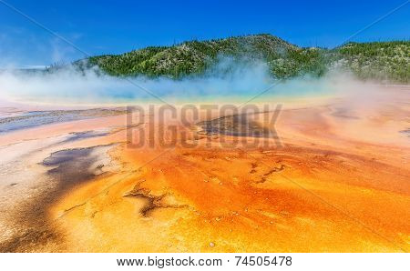 Hot volcanic spring of yellow and orange color in Yellowstone.