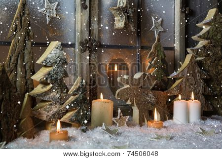 Handmade christmas decoration with wooden trees and reindeer decorated in the window.