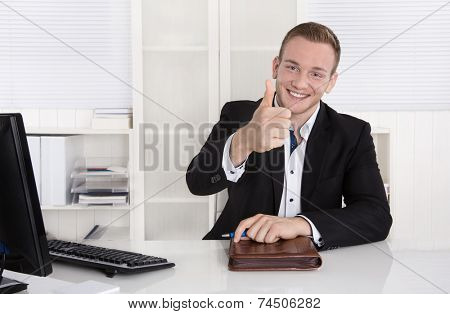 Happy young businessman sitting in his office making thumb up gesture.