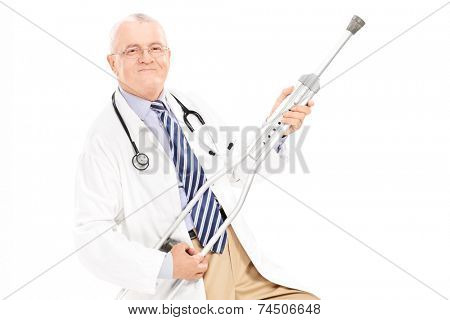 Mature doctor playing guitar on a crutch isolated on white background