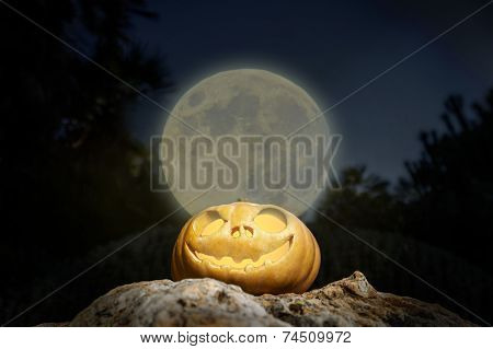 Spooky Halloween Pumpkin In Moon Light On A Rock