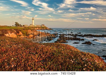 The ocean coast, rocks and lighthouse on sunset.
