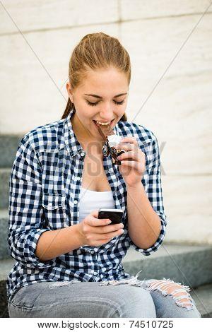 Teenager eating chcolate looking in phone