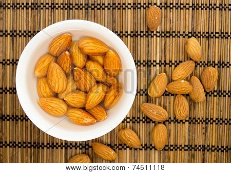 Soaked Almonds In A Bowl Against A Straw Mat