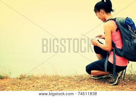 woman hiker use digital tablet on seaside trail