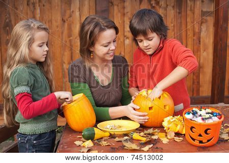 Woman helping kids to carve jack-o-lanterns for Halloween