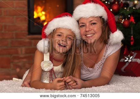 Happy mother and daughter celebrating Christmas together - laying by the tree and fire