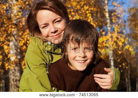 Woman and her son on an autumn stroll in the sunny forest - closeup portrait