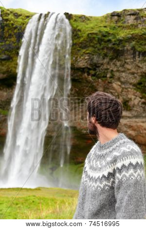 Icelandic sweater man by waterfall on Iceland outdoor smiling. Portrait of good looking male model  in nature landscape with tourist attraction Seljalandsfoss waterfall on Ring Road.